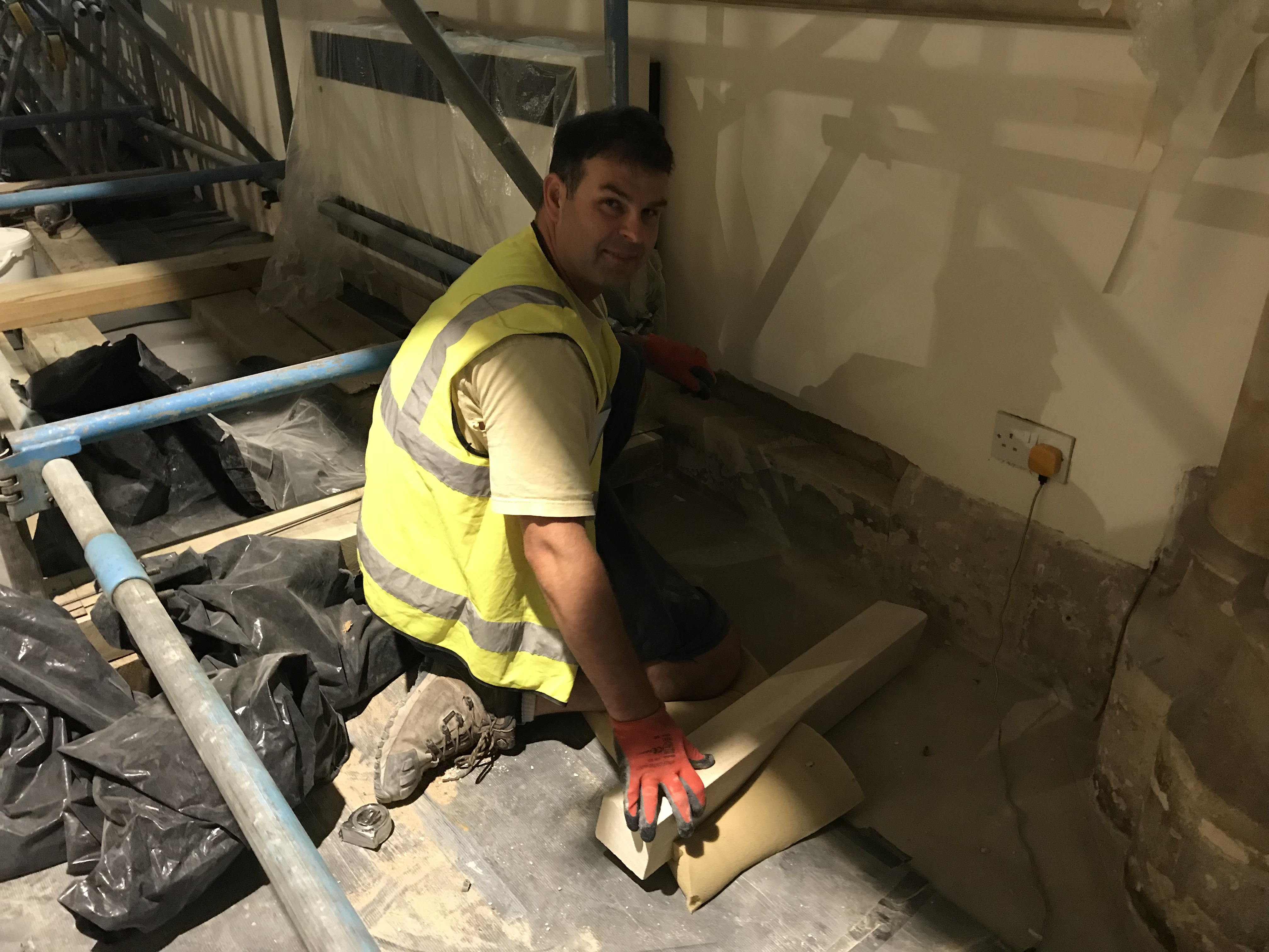 Jiri (stone mason) replacing damaged skirting with new bathstone on the North West side.